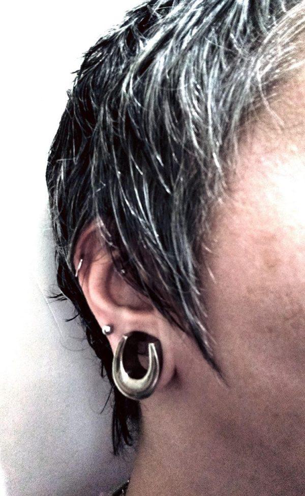 alargador meia lua prateado, usando em orelha grande.